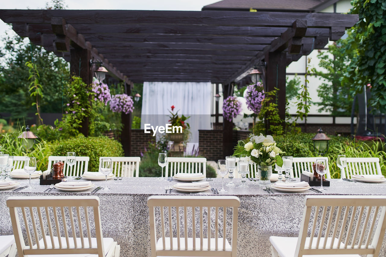 POTTED PLANTS ON TABLE BY EMPTY CHAIRS AND TABLES IN FOREGROUND
