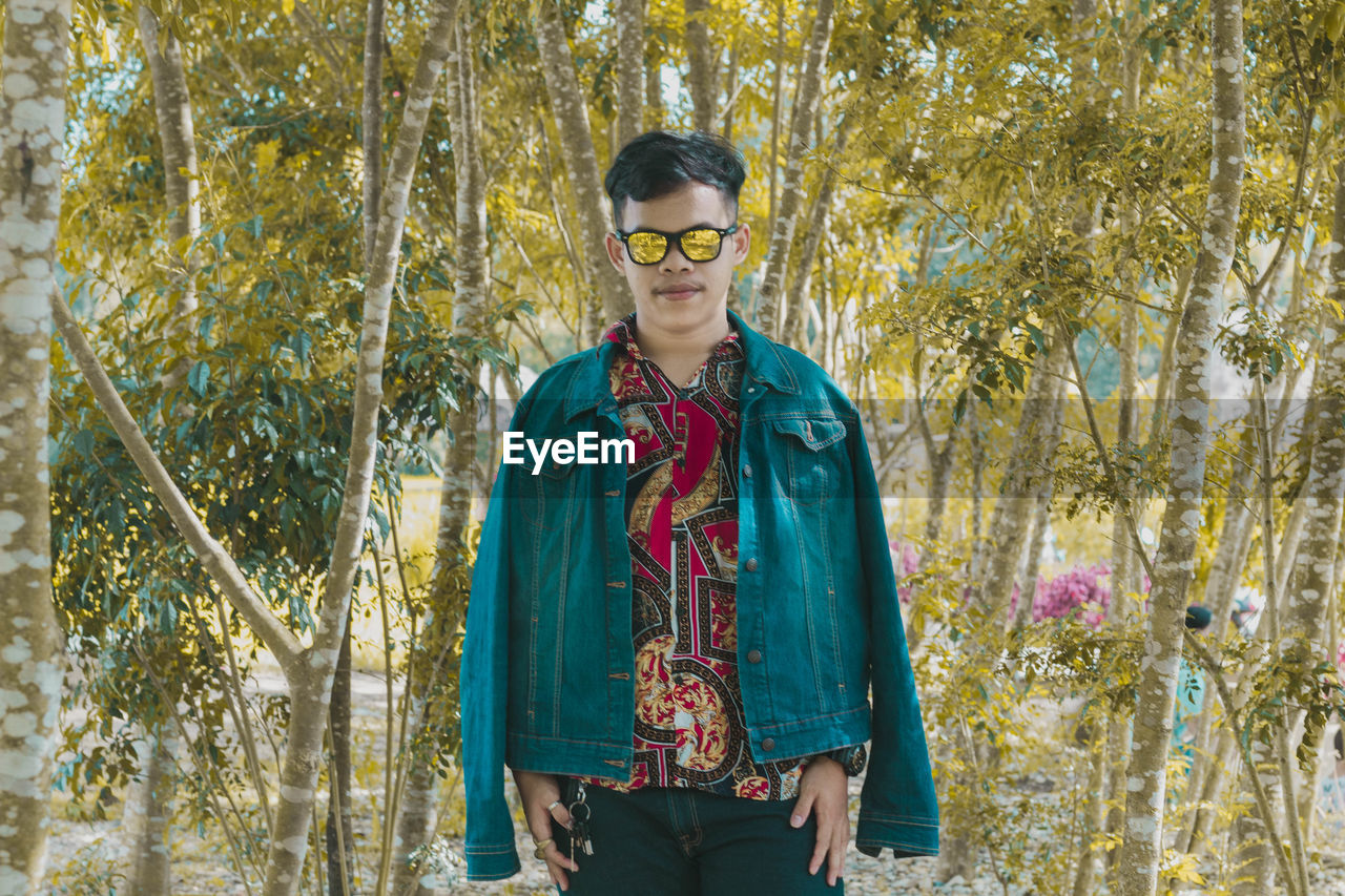 standing, one person, glasses, plant, front view, portrait, tree, looking at camera, eyeglasses, young adult, nature, day, three quarter length, casual clothing, fashion, young men, leisure activity, waist up, outdoors, teenager, hairstyle