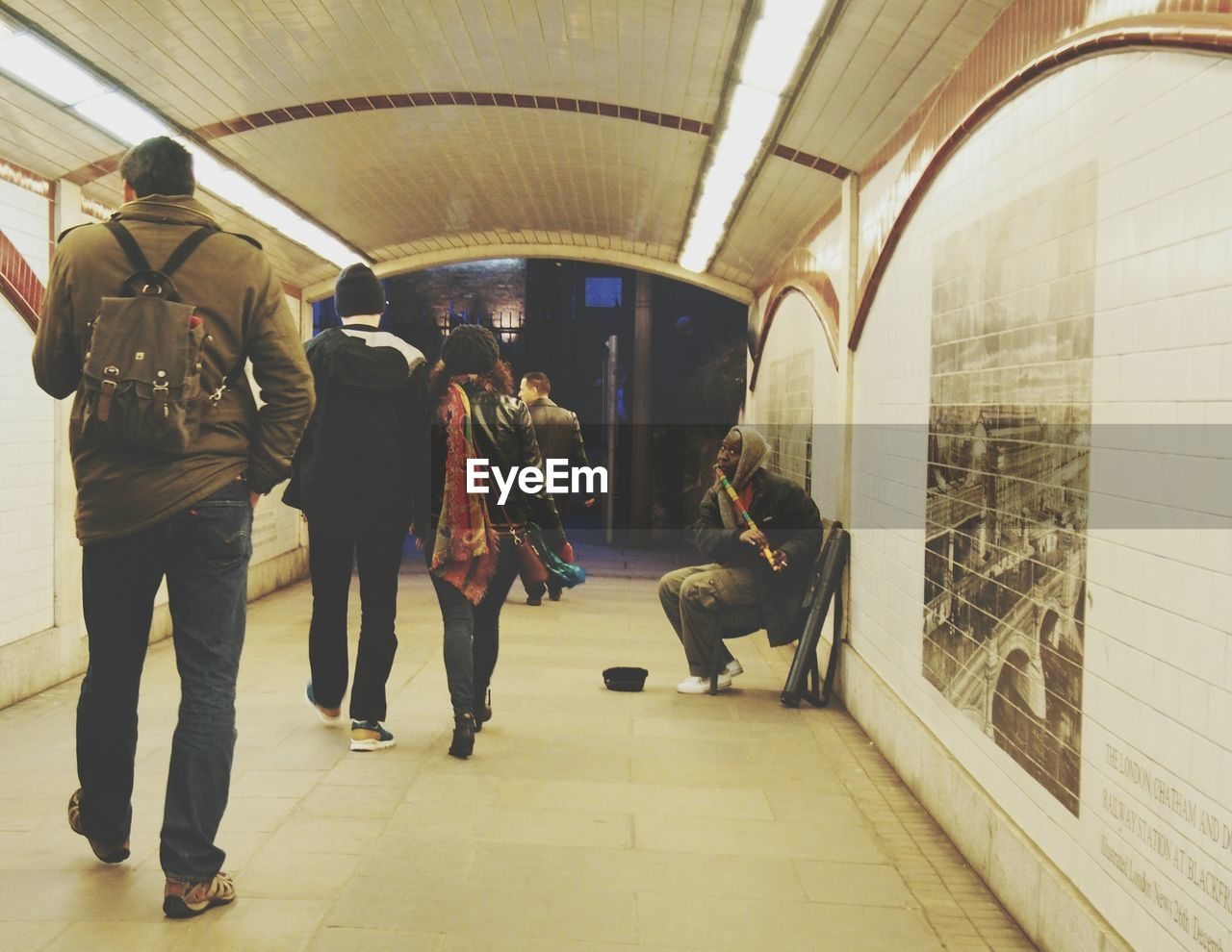 real people, men, lifestyles, leisure activity, full length, casual clothing, women, indoors, rear view, transportation, standing, subway station, togetherness, sitting, day, adult, people