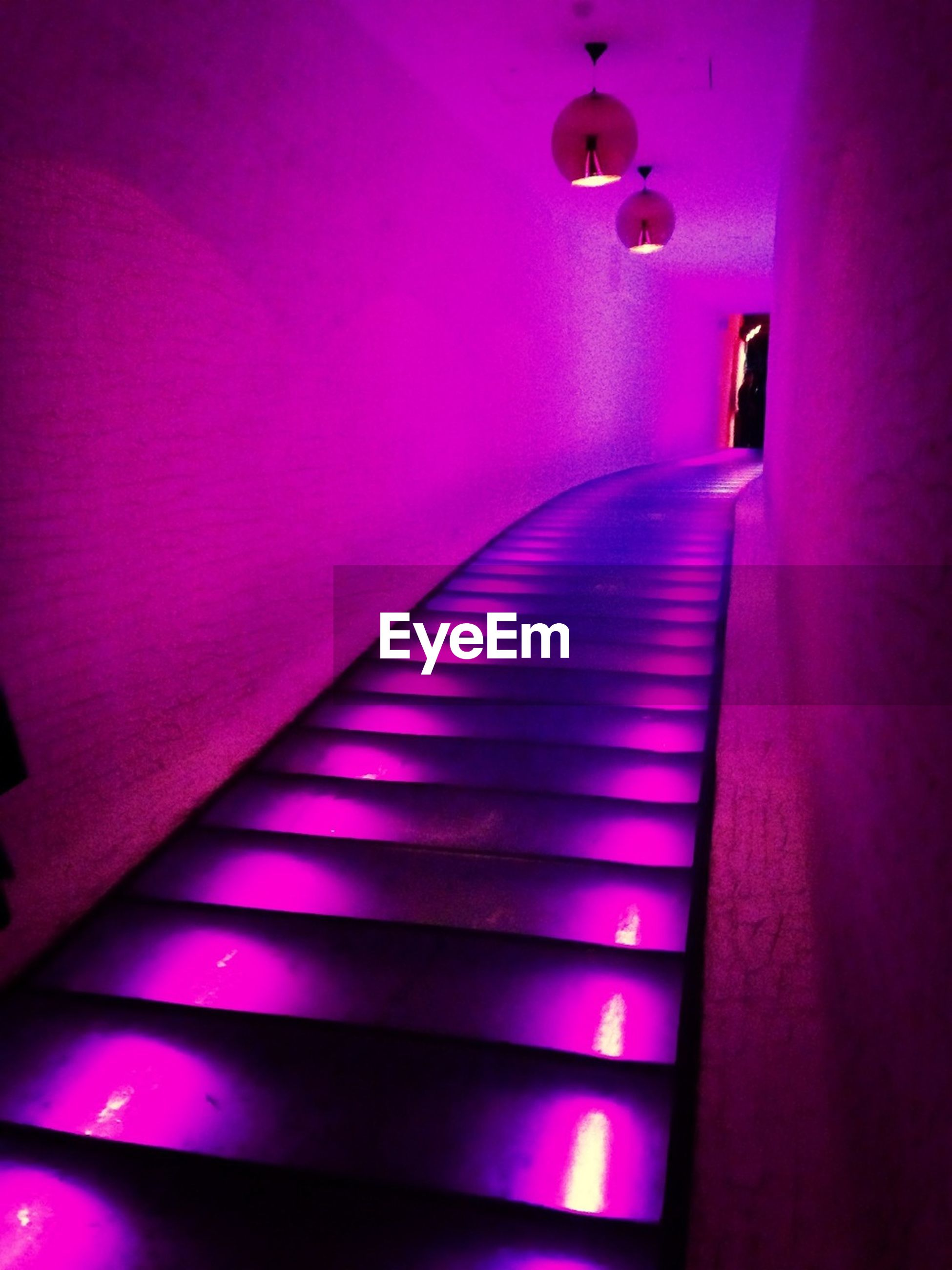 indoors, illuminated, staircase, steps, steps and staircases, lighting equipment, wall - building feature, light - natural phenomenon, the way forward, escalator, railing, modern, pattern, absence, built structure, architecture, ceiling, no people, low angle view, empty