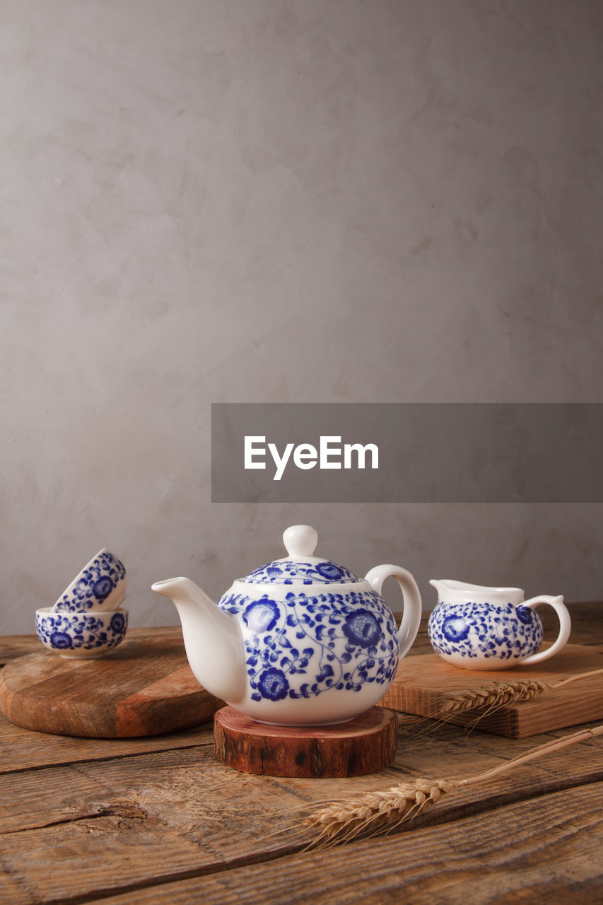 HIGH ANGLE VIEW OF VARIOUS TEA ON TABLE AGAINST WALL