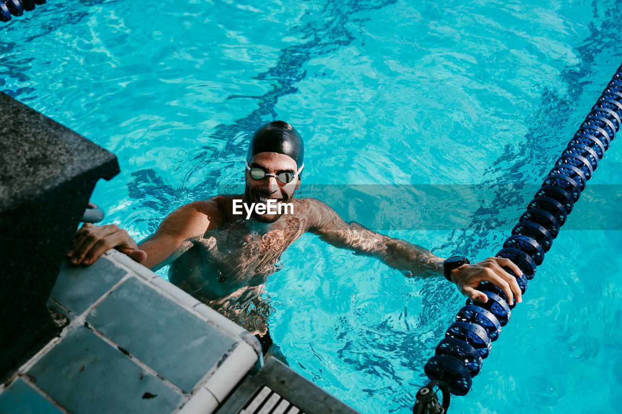 HIGH ANGLE VIEW OF A MAN SWIMMING IN POOL