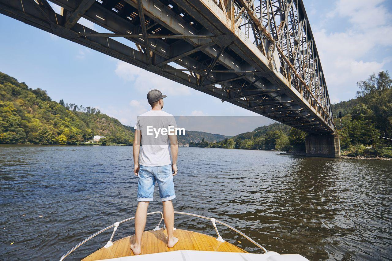 Rear view of man standing on boat in river below bridge