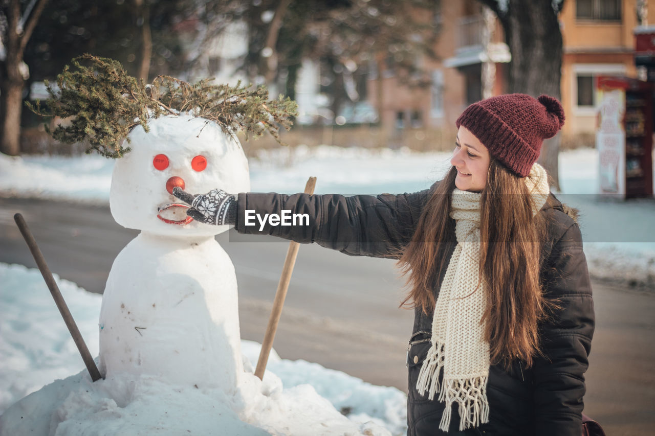 Smiling Woman Touching Snowman In City