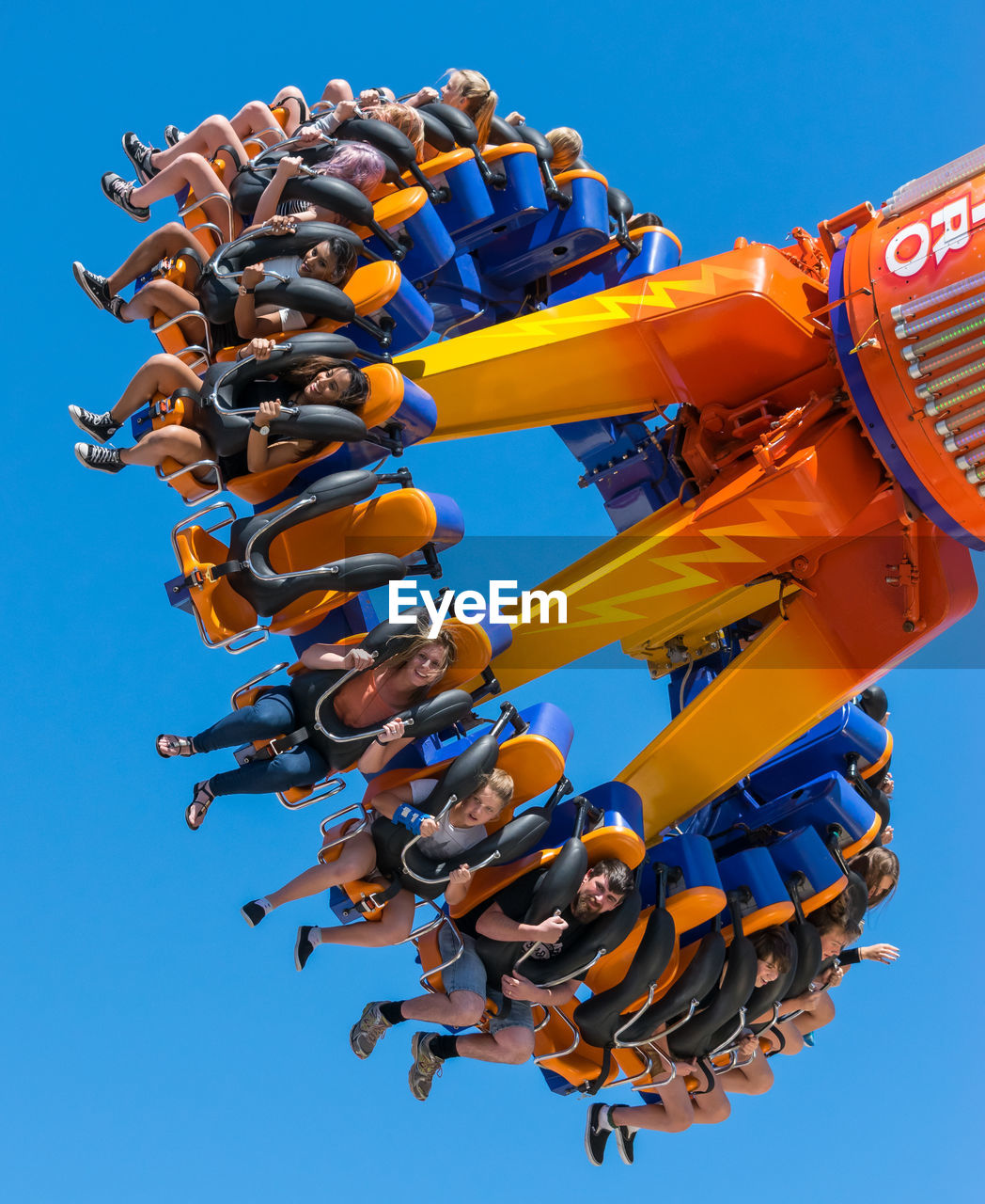 sky, low angle view, clear sky, day, blue, nature, amusement park, amusement park ride, no people, arts culture and entertainment, outdoors, sunlight, yellow, in a row, cooperation, multi colored, enjoyment, orange color, teamwork