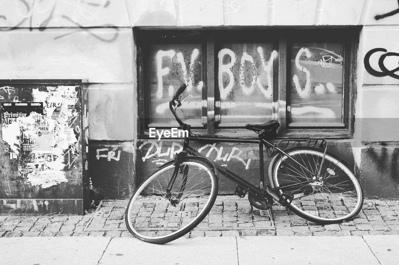 bicycle, architecture, transportation, land vehicle, building exterior, mode of transportation, built structure, wall - building feature, day, no people, stationary, text, graffiti, wall, outdoors, communication, parking, city, footpath, building, wheel