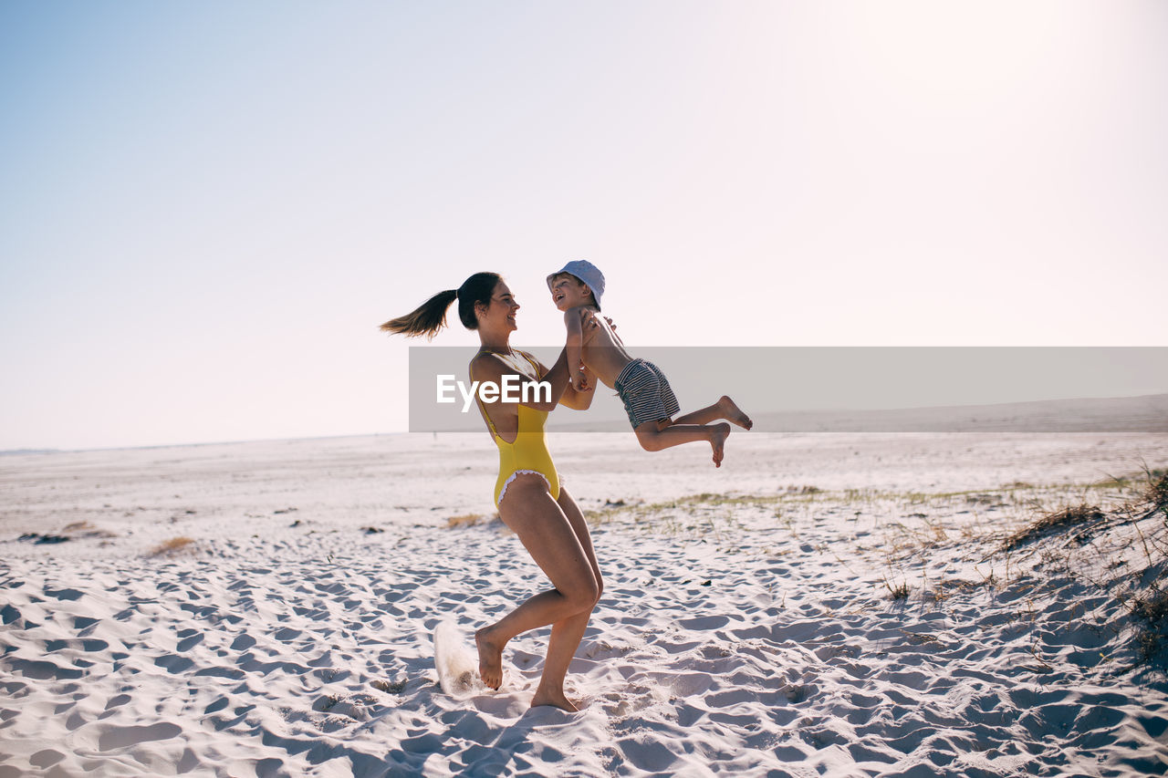 beach, sky, land, sea, two people, leisure activity, real people, clear sky, full length, lifestyles, sand, horizon, water, adult, beauty in nature, young adult, togetherness, women, nature, young women, horizon over water, positive emotion