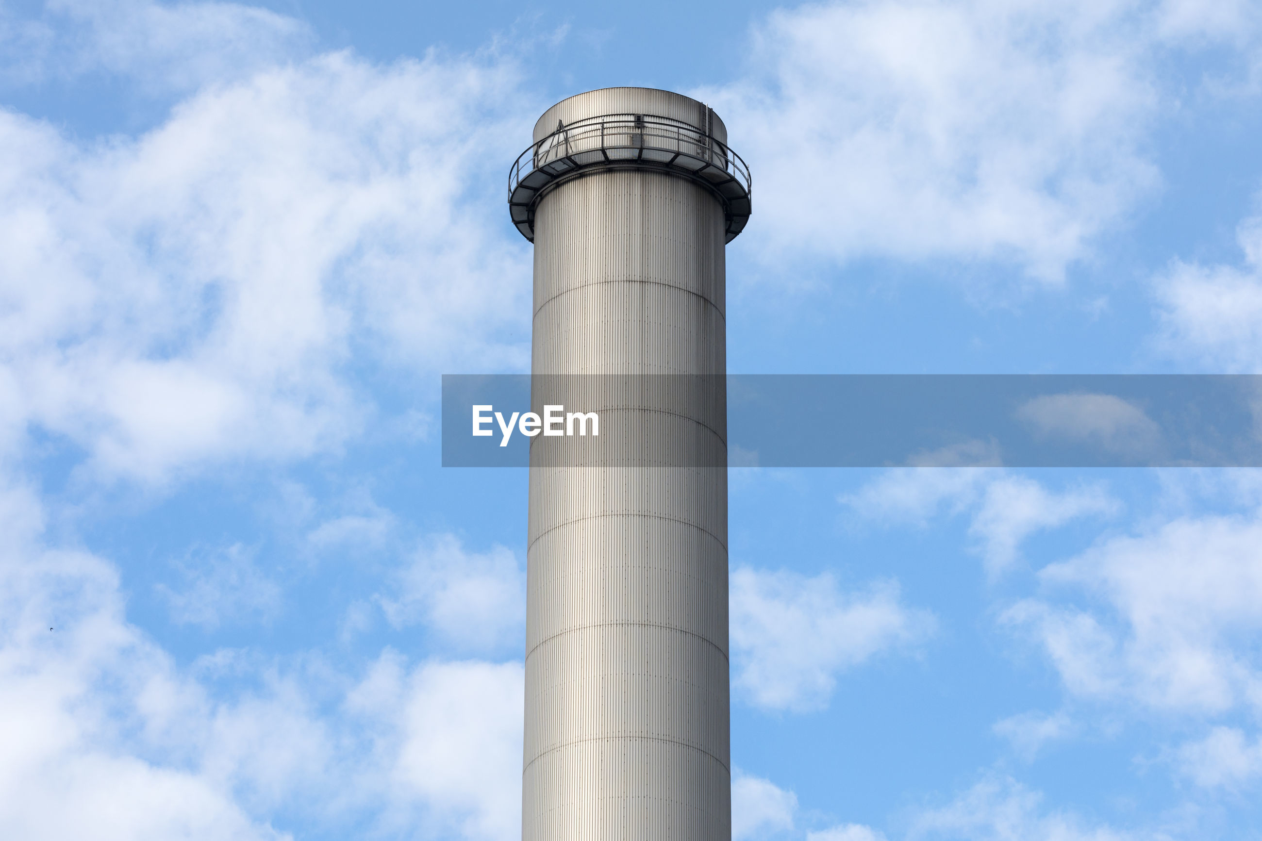 Low angle view of smoke stack against cloudy sky