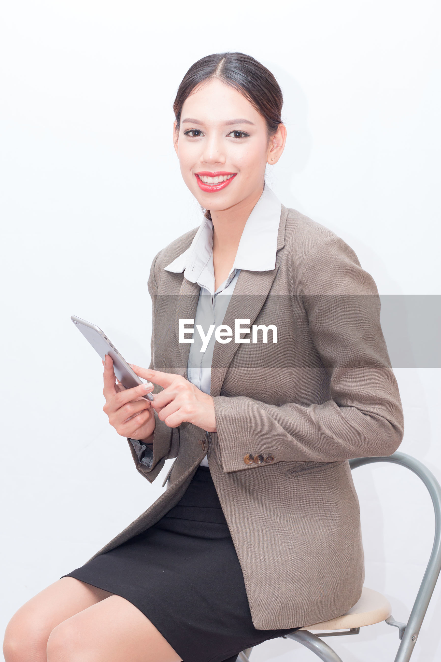 Portrait of businesswoman using digital tablet against white background