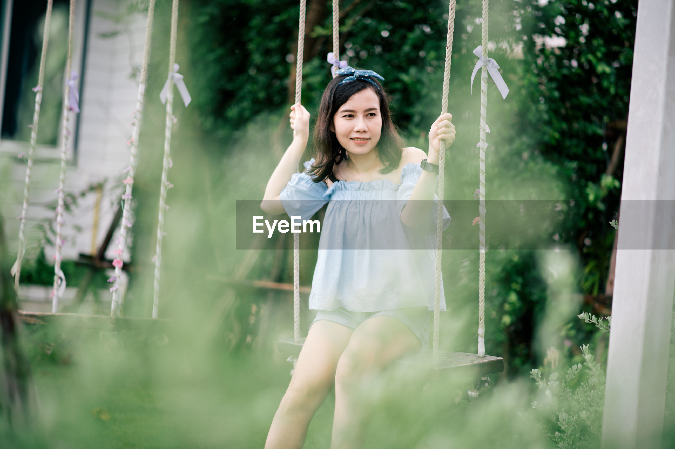 Woman sitting on swing at park