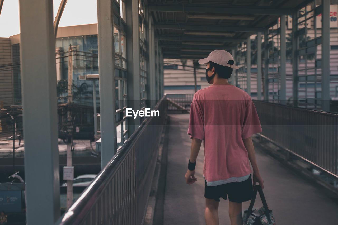 Rear View Of Man Walking On Footbridge In City