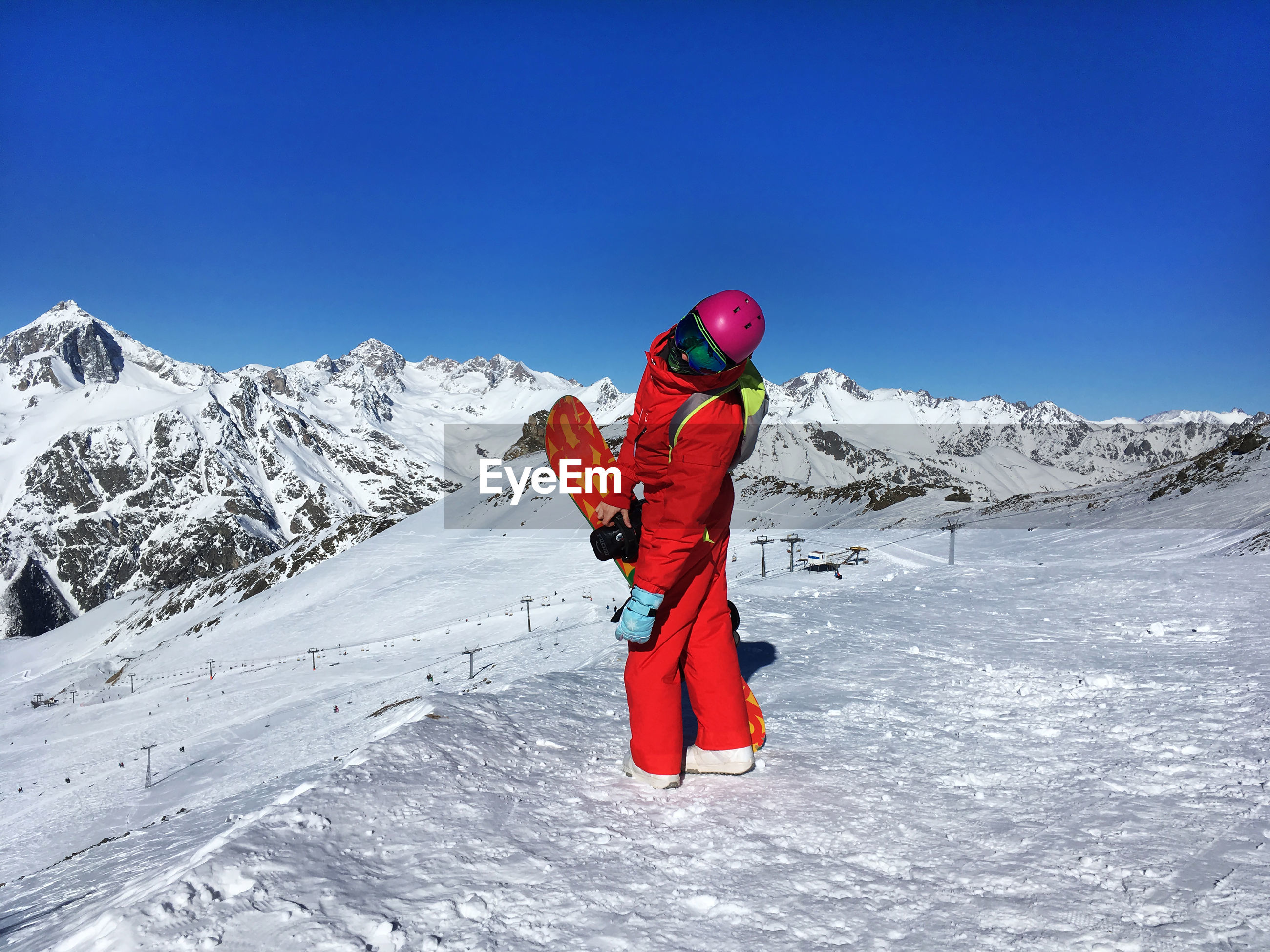Full length of woman standing against snowcapped mountains
