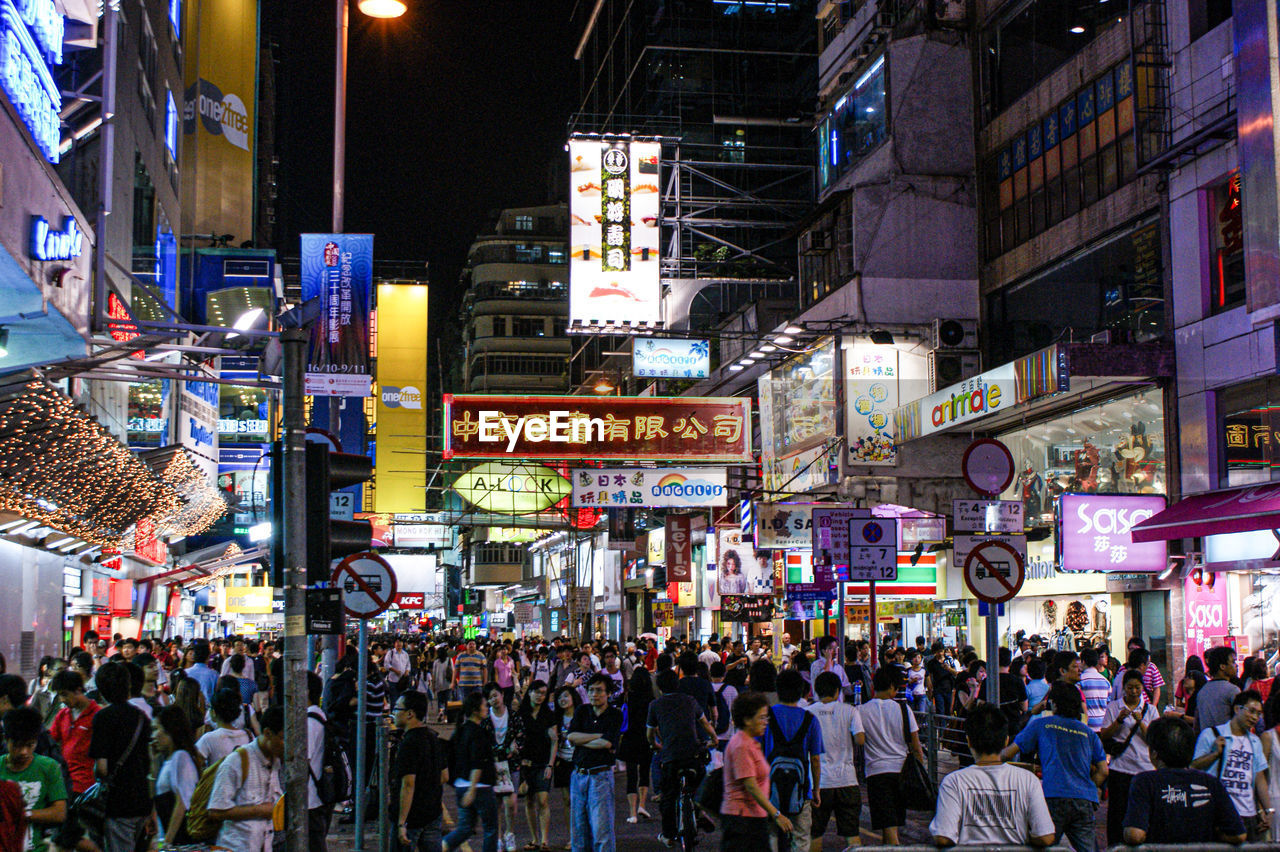 city, building exterior, architecture, crowd, built structure, street, group of people, night, large group of people, illuminated, real people, city life, city street, advertisement, billboard, text, communication, building, commercial sign, lifestyles, outdoors, neon, consumerism, office building exterior, skyscraper, nightlife