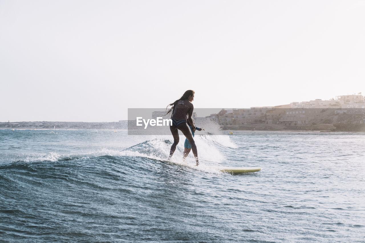 MAN IN SEA AGAINST CLEAR SKY