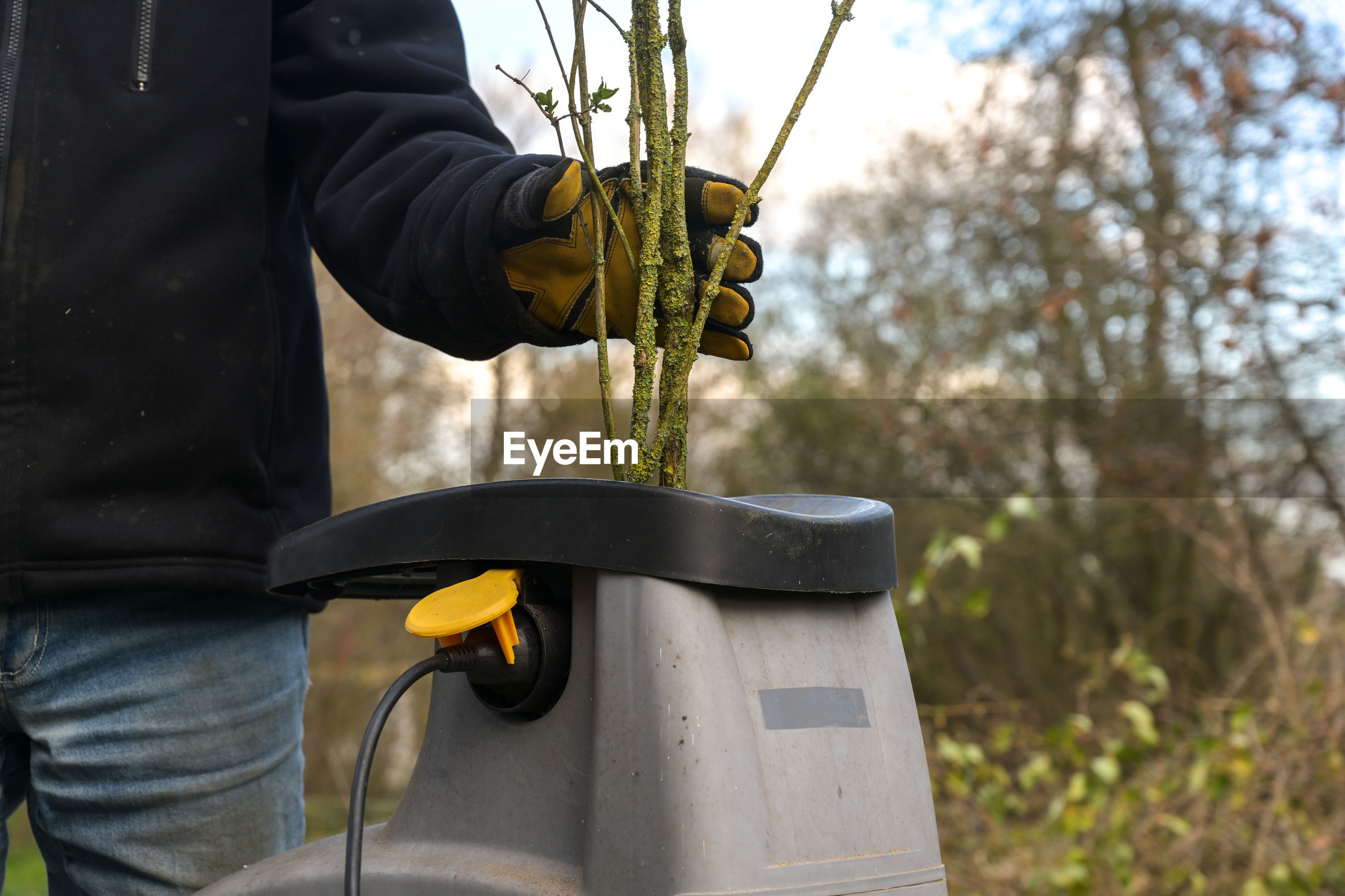 Midsection of man putting plants in machinery outdoors
