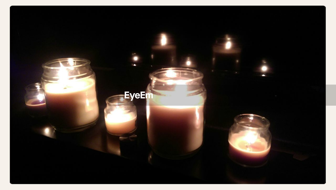 flame, candle, fire - natural phenomenon, burning, tea light, illuminated, glowing, heat - temperature, black background, no people, table, darkroom, indoors, close-up, studio shot