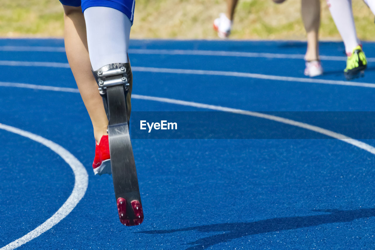 Low Section Of Athlete With Artificial Limb Running On Track