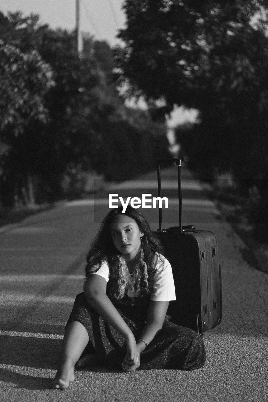 Portrait Of Young Woman Sitting With Luggage On Road