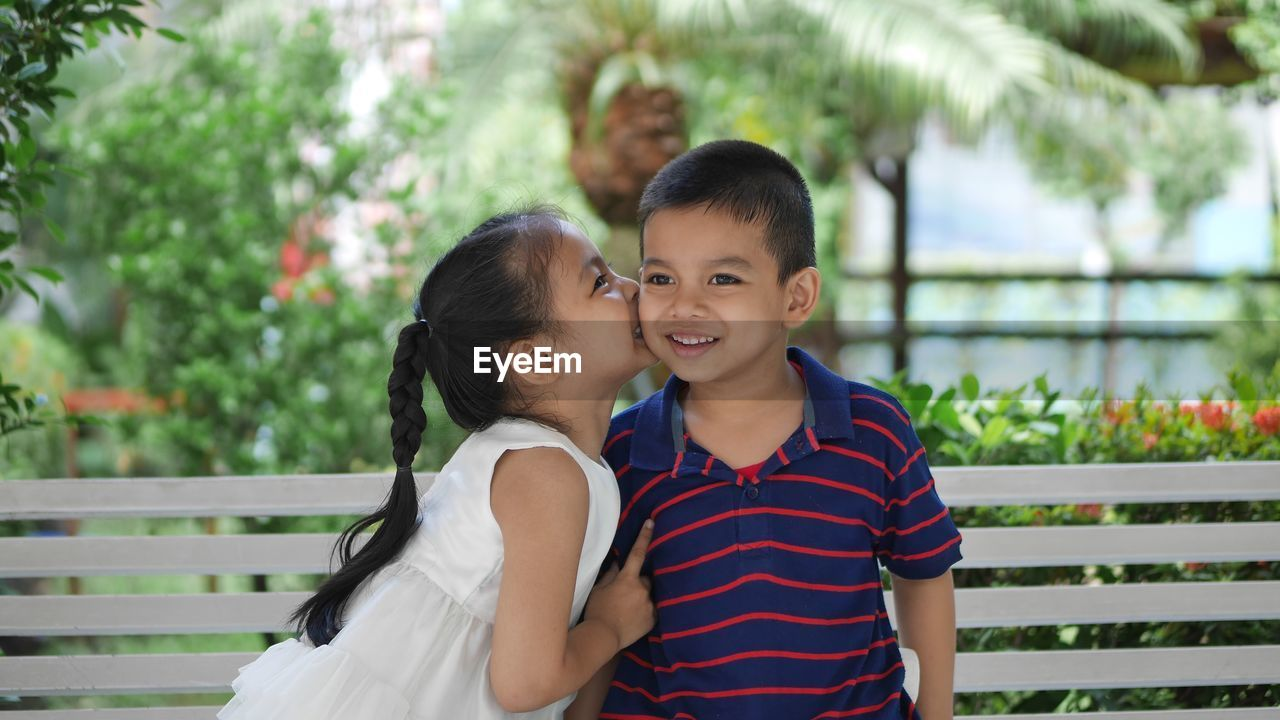 Smiling girl kissing brother on cheek while sitting on bench