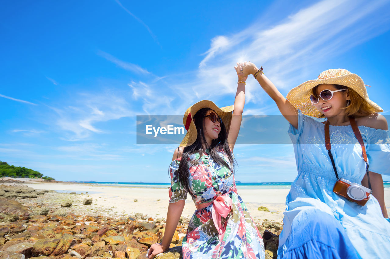 Excited women wearing sunglasses at beach against sky