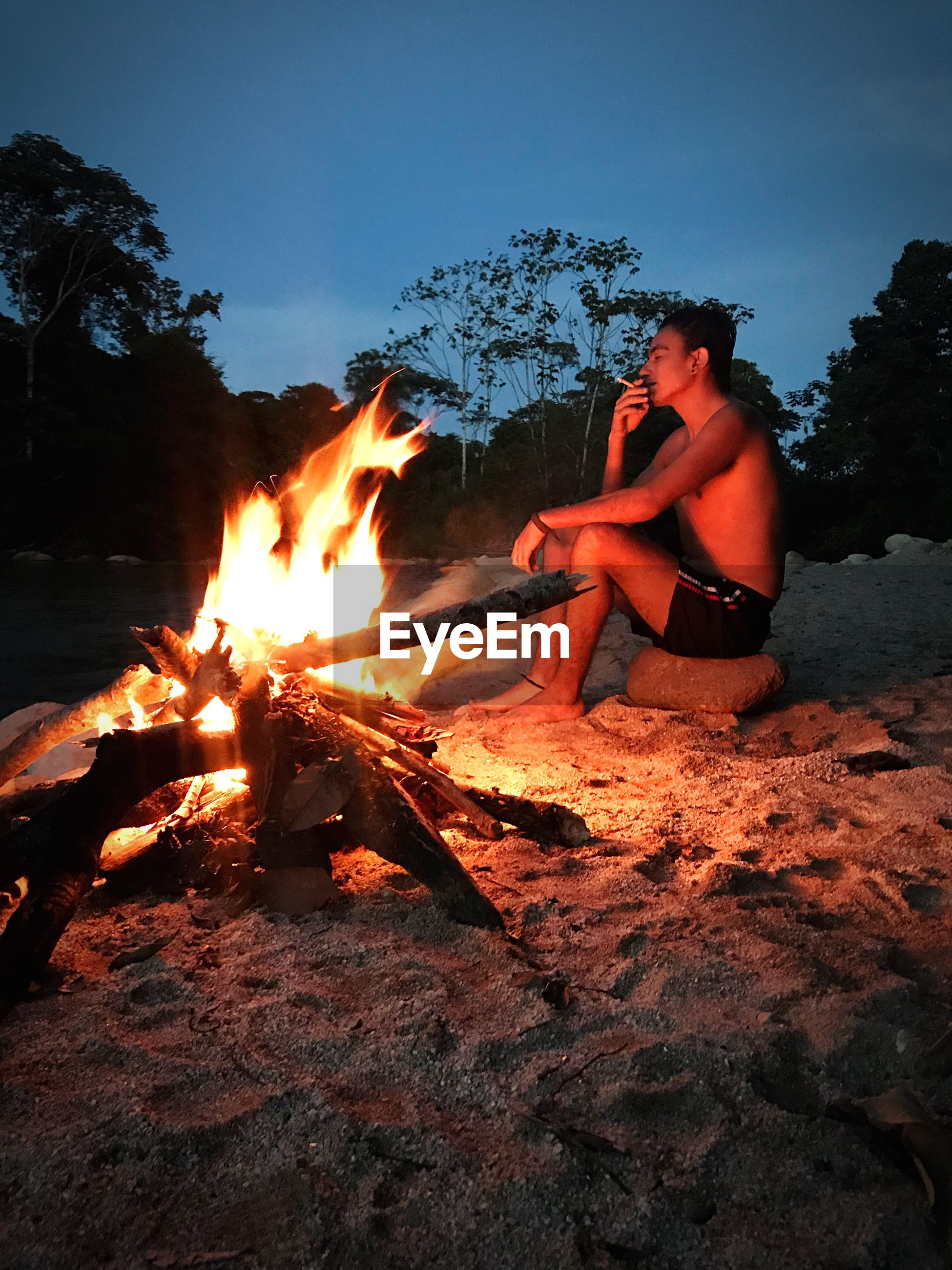 Side view of shirtless man smoking while sitting by campfire