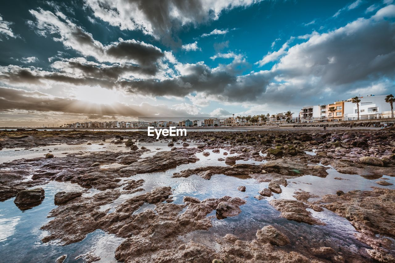 cloud - sky, sky, water, rock, nature, rock - object, beauty in nature, solid, beach, scenics - nature, no people, land, tranquility, sea, building exterior, architecture, built structure, day