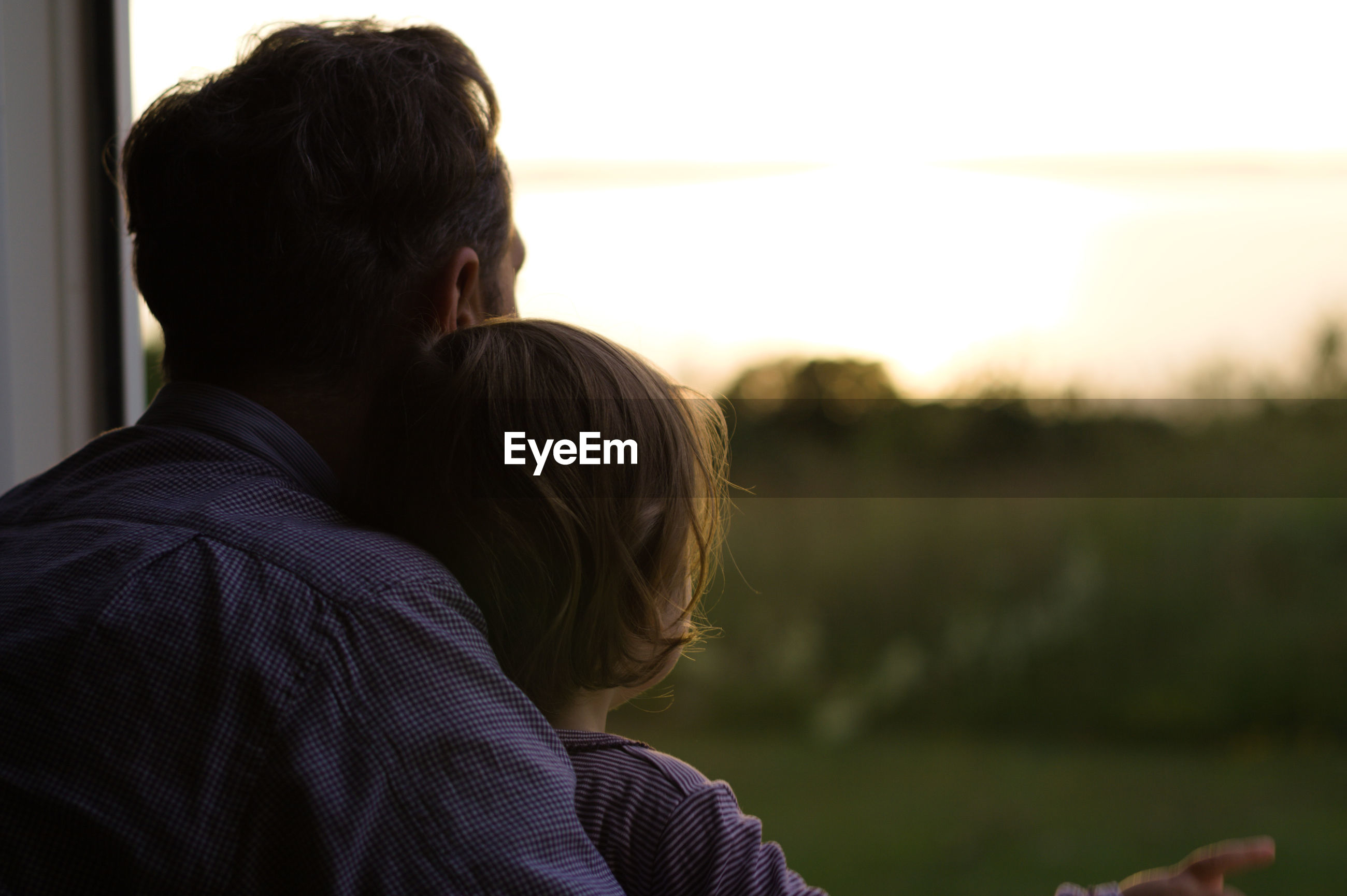Rear view of father and daughter looking at sunset through window