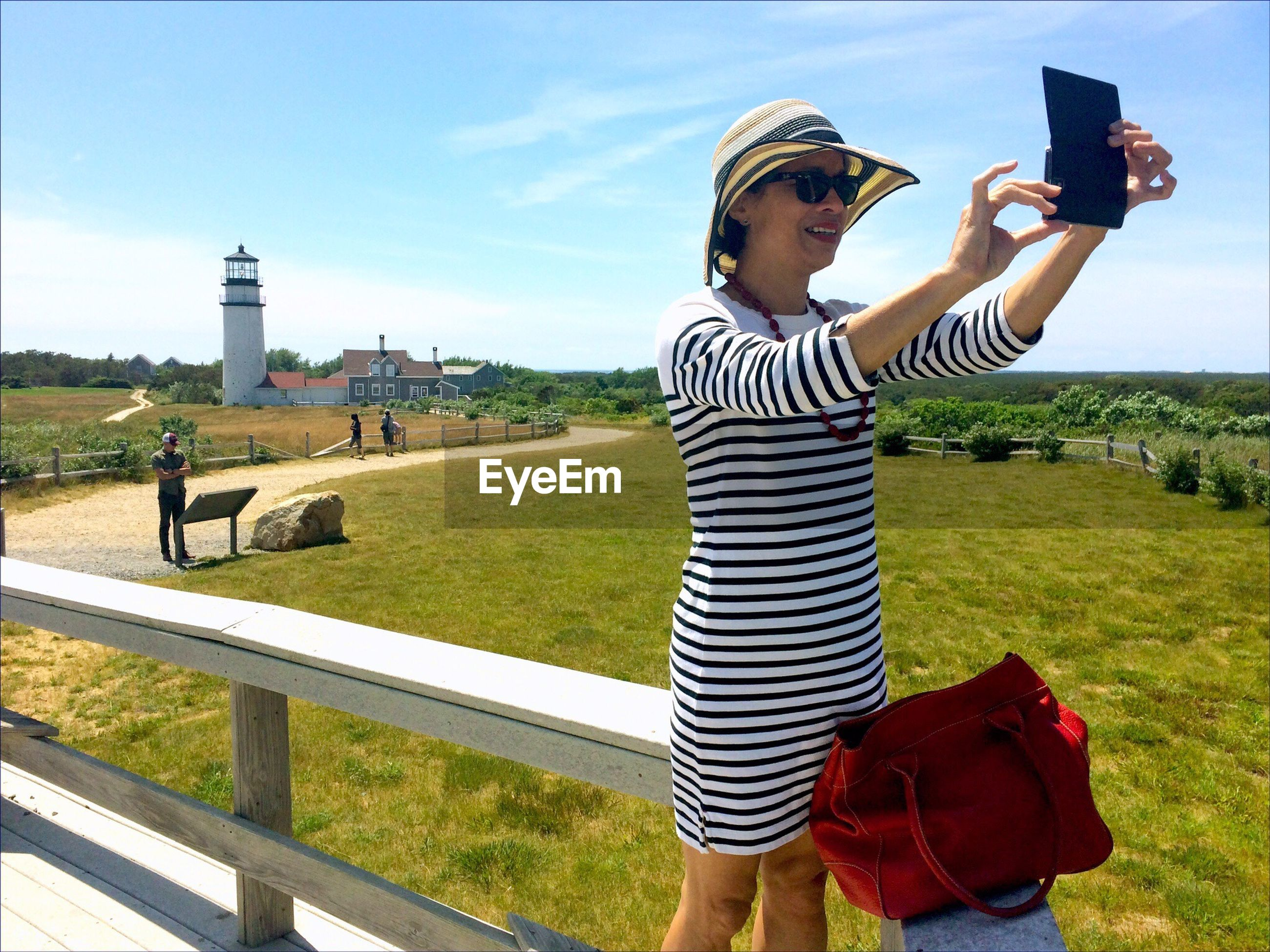Woman taking selfie against lighthouse