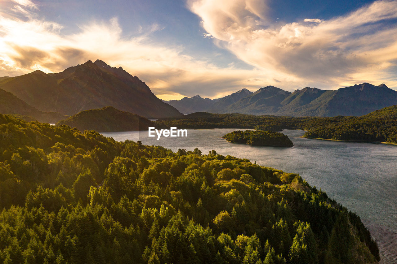 Scenic view of lake by mountains against sky during sunset