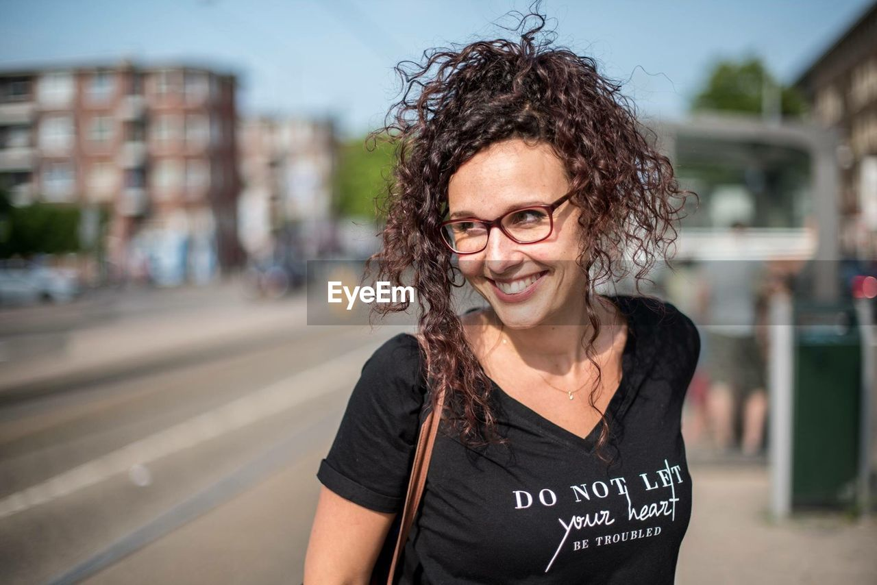 smiling, portrait, looking at camera, happiness, one person, emotion, front view, focus on foreground, women, casual clothing, adult, brown hair, hairstyle, toothy smile, teeth, curly hair, beauty, hair, waist up, standing, beautiful woman