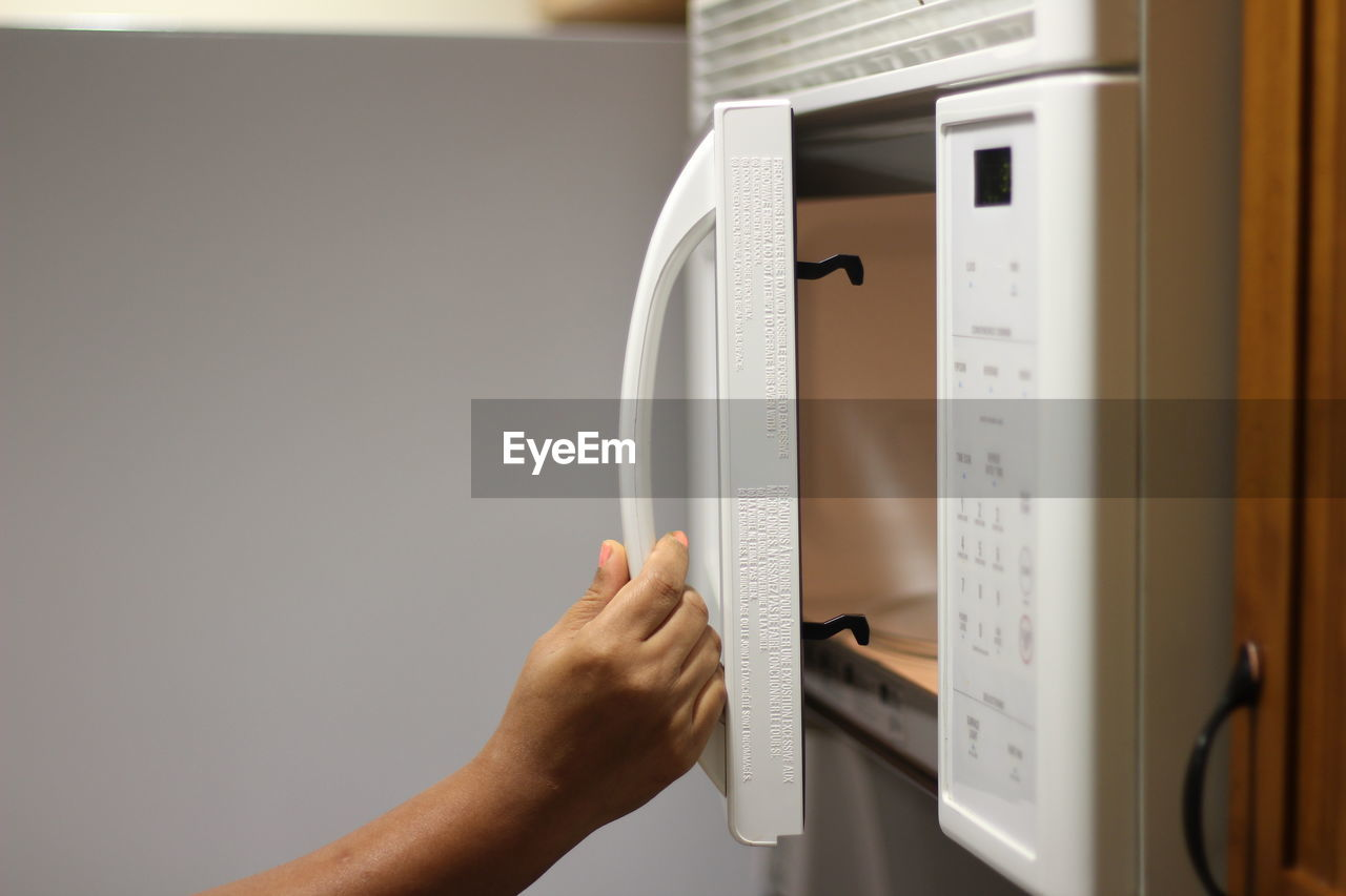 View Of Hand Opening Microwave At Home