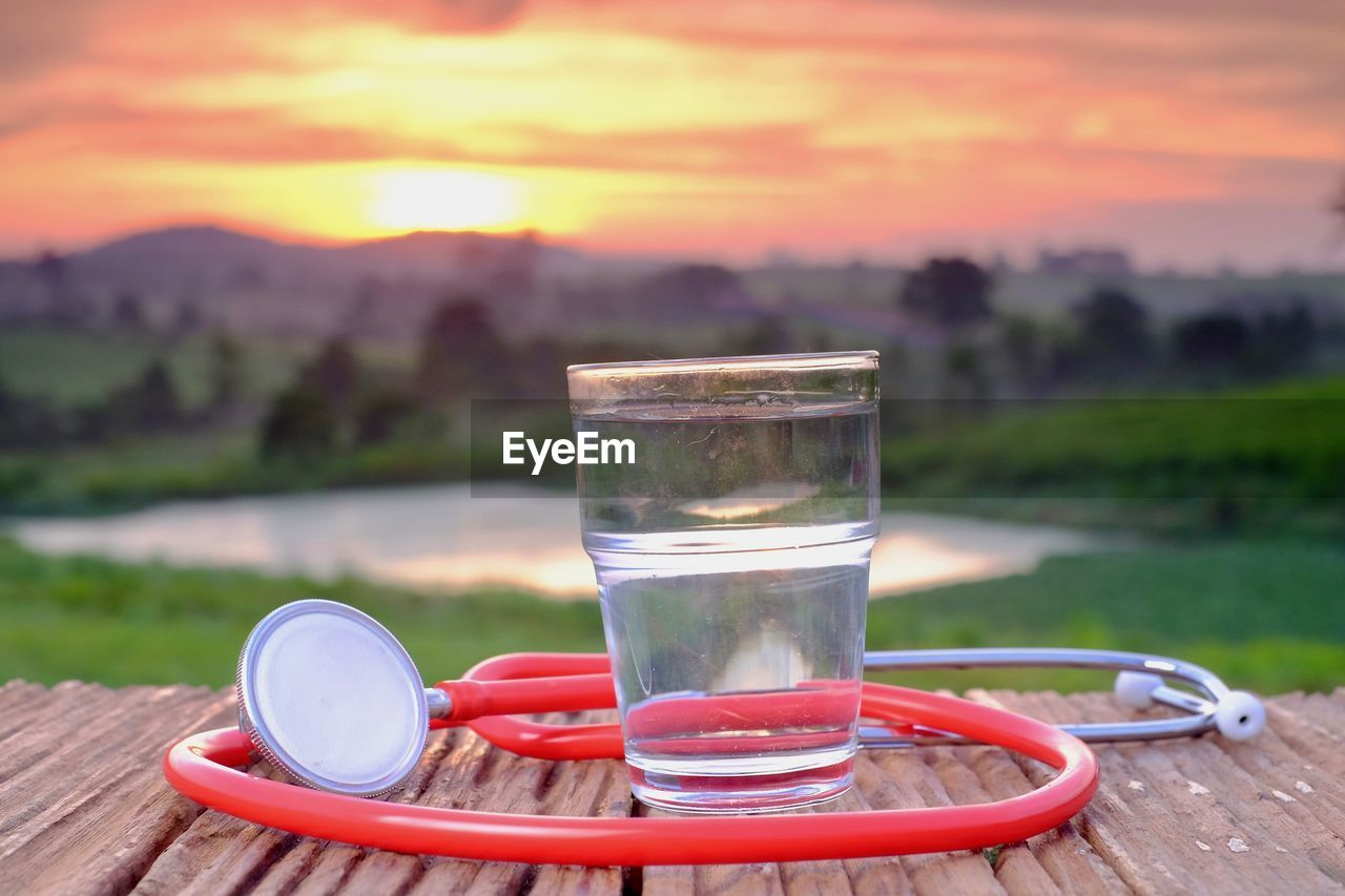 drink, table, glass, refreshment, water, sunset, food and drink, nature, focus on foreground, sky, drinking glass, household equipment, close-up, freshness, no people, beauty in nature, scenics - nature, transparent, glass - material, outdoors