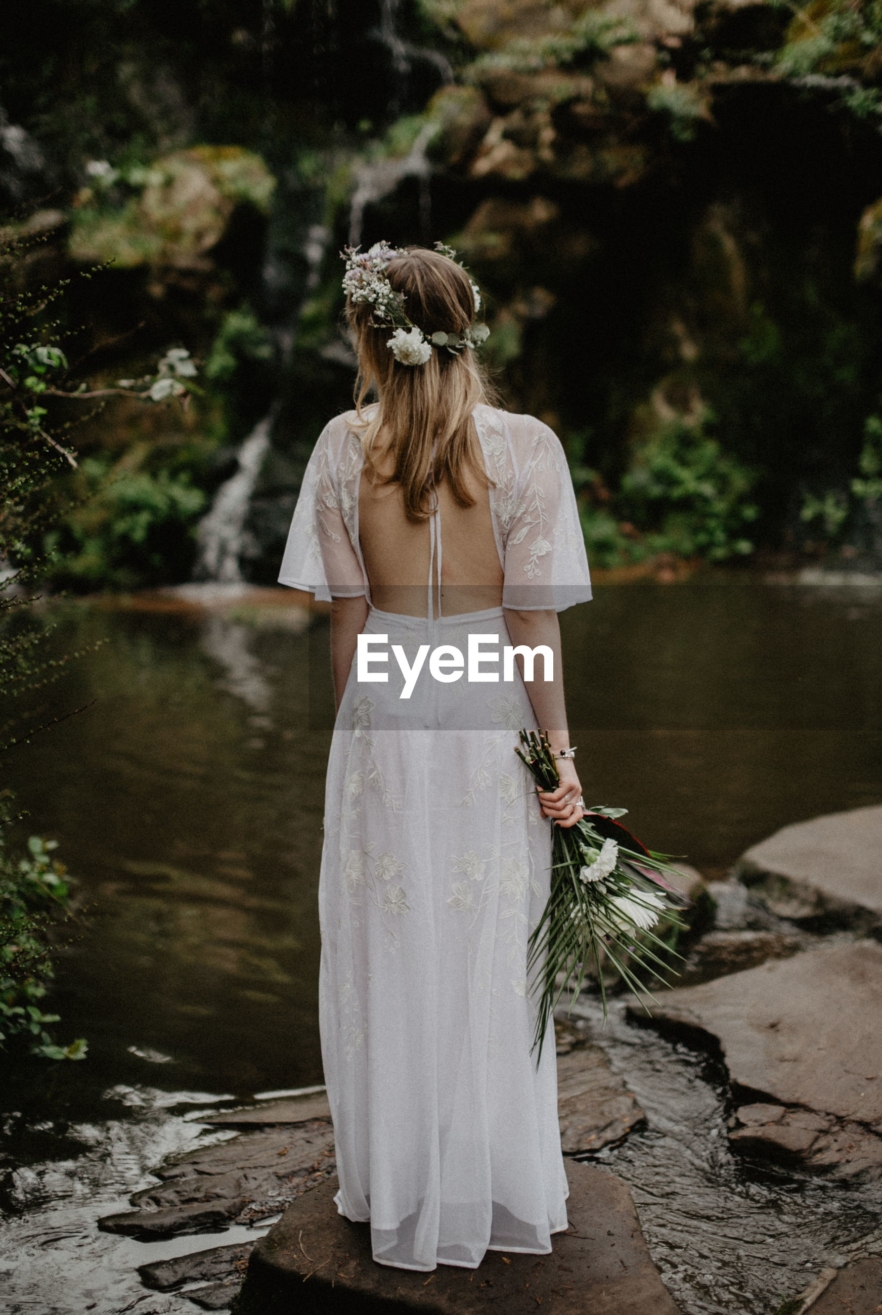 Rear view of bride standing by lake
