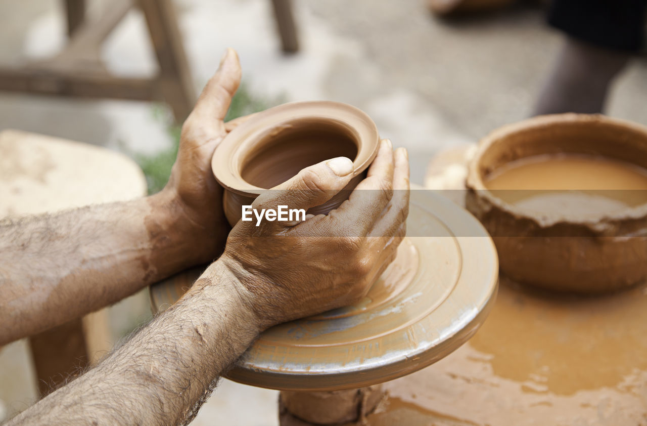 human hand, one person, hand, real people, focus on foreground, holding, pottery, human body part, working, skill, clay, occupation, craft, indoors, men, art and craft, food and drink, molding a shape, preparation, finger