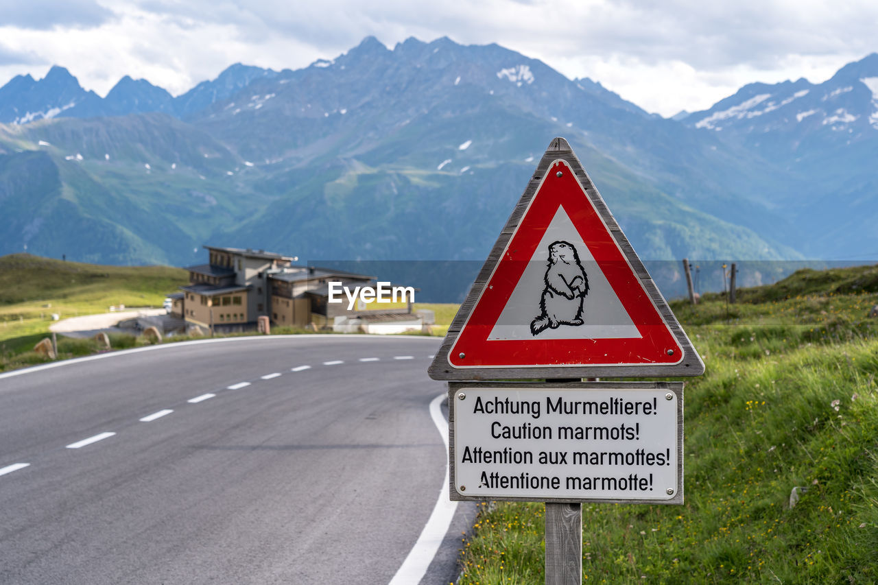 Information sign on road by mountains against sky
