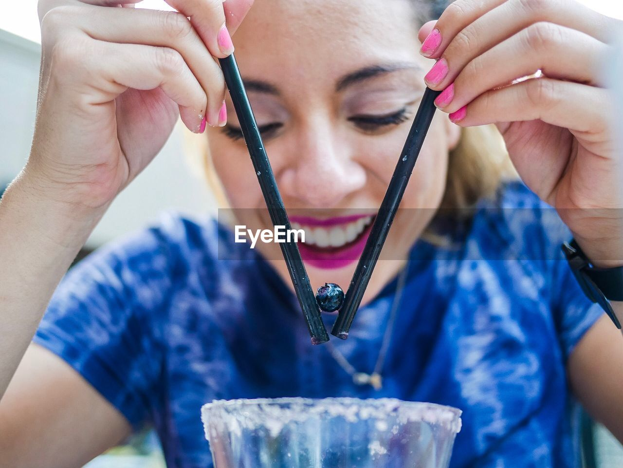 Happy Woman Picking Up Blueberry With Drinking Straws Over Glass