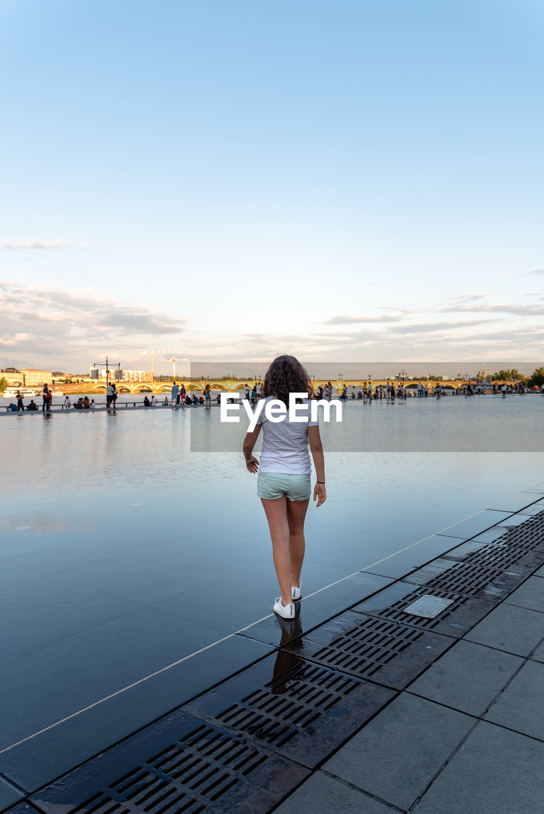 Rear view of teenage girl walking in city against sky