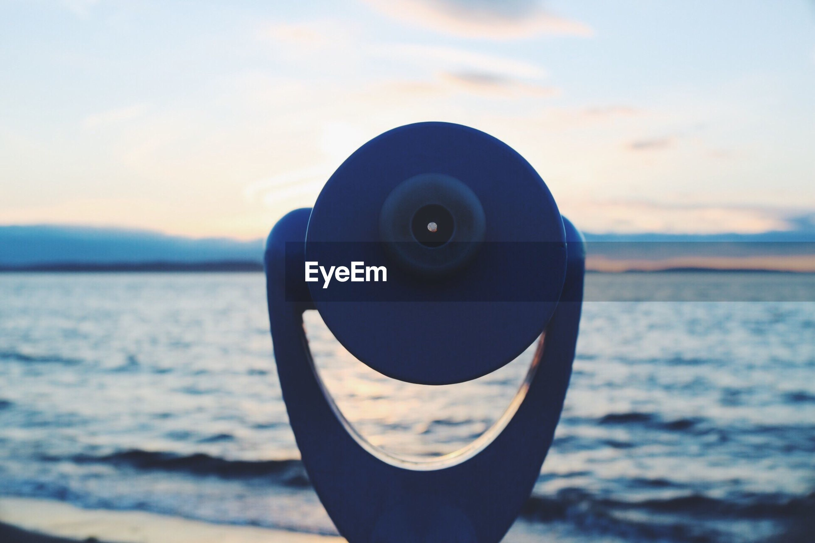 CLOSE-UP OF COIN-OPERATED BINOCULARS AGAINST SEA DURING SUNSET