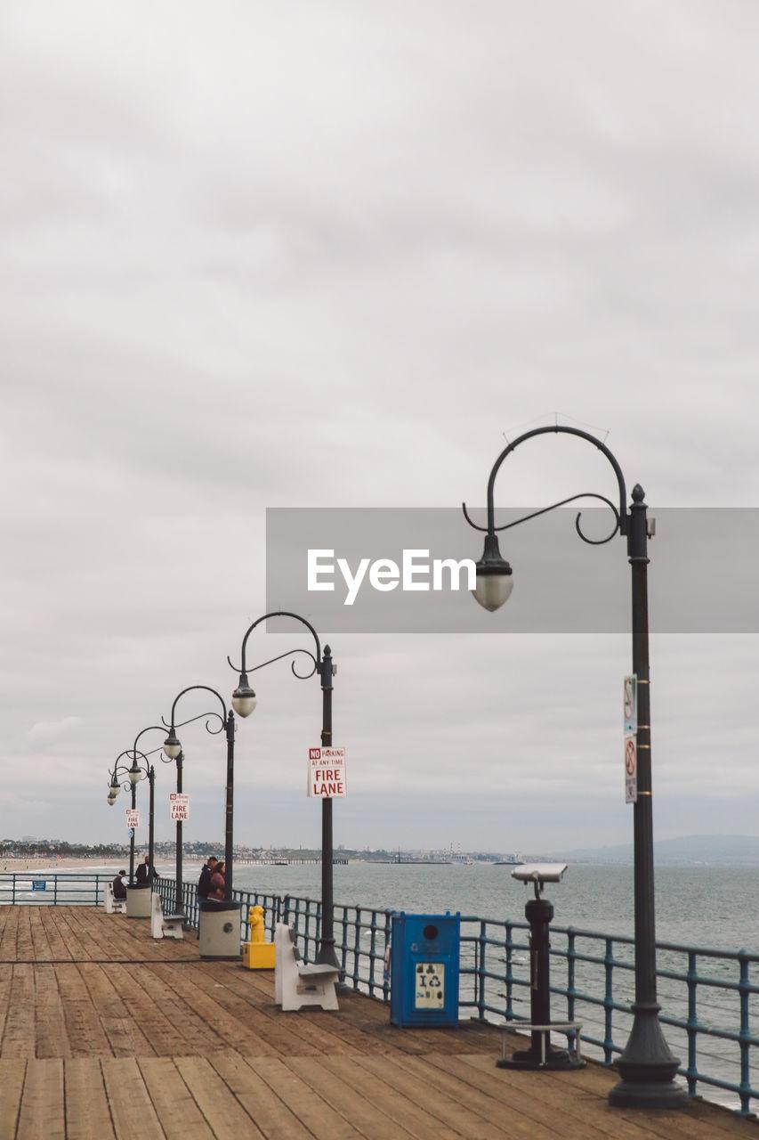sea, water, sky, railing, lighting equipment, street light, cloud - sky, day, no people, horizon over water, nature, outdoors