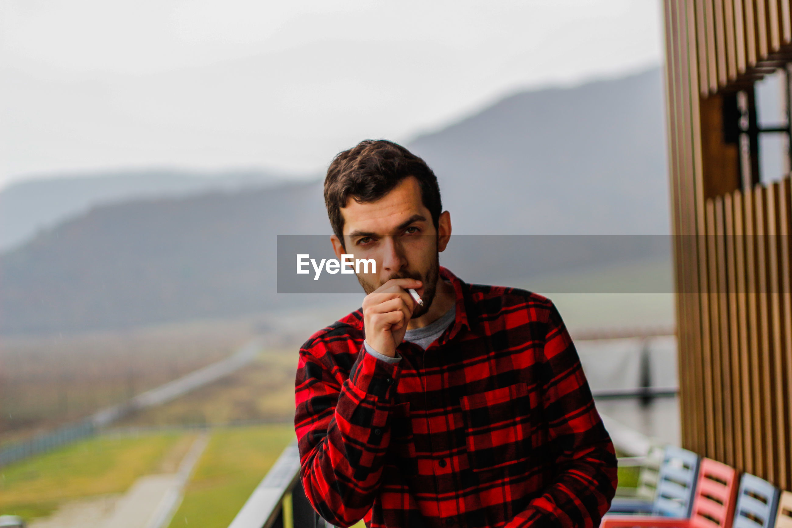 Portrait of handsome young man smoking cigarette against clear sky