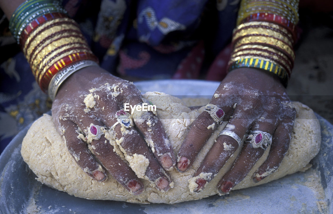 Close-Up Of Hands With Rings Preparing Dough