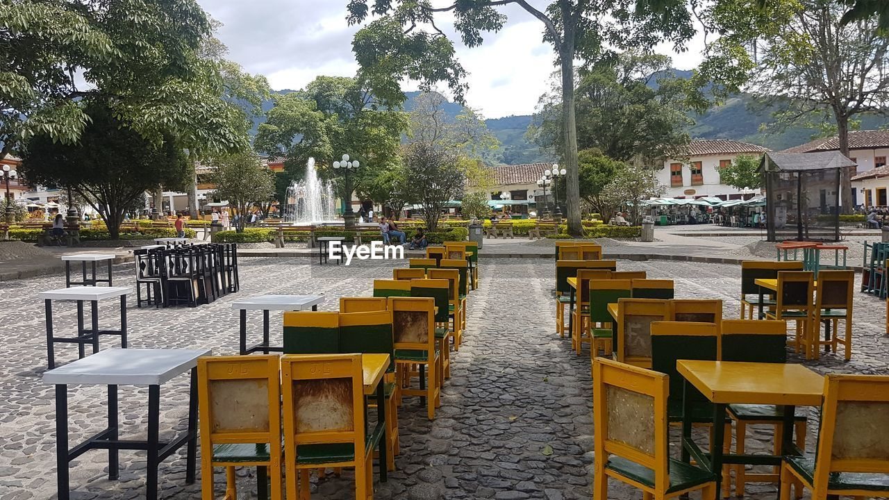 plant, tree, seat, table, architecture, chair, day, cafe, built structure, nature, empty, city, building exterior, restaurant, street, sidewalk cafe, incidental people, outdoors, water