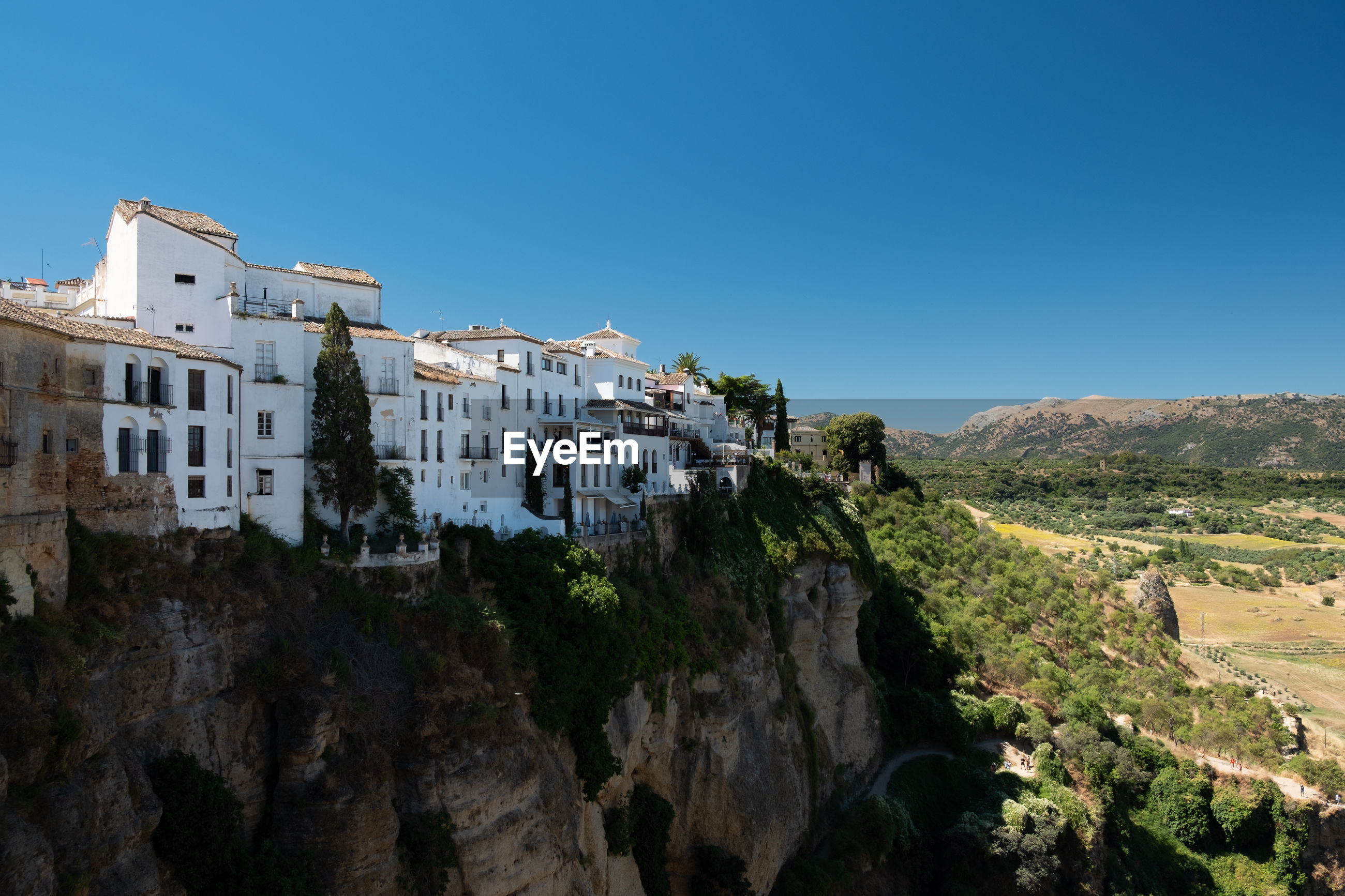 Panoramic view of buildings and mountains against clear blue sky