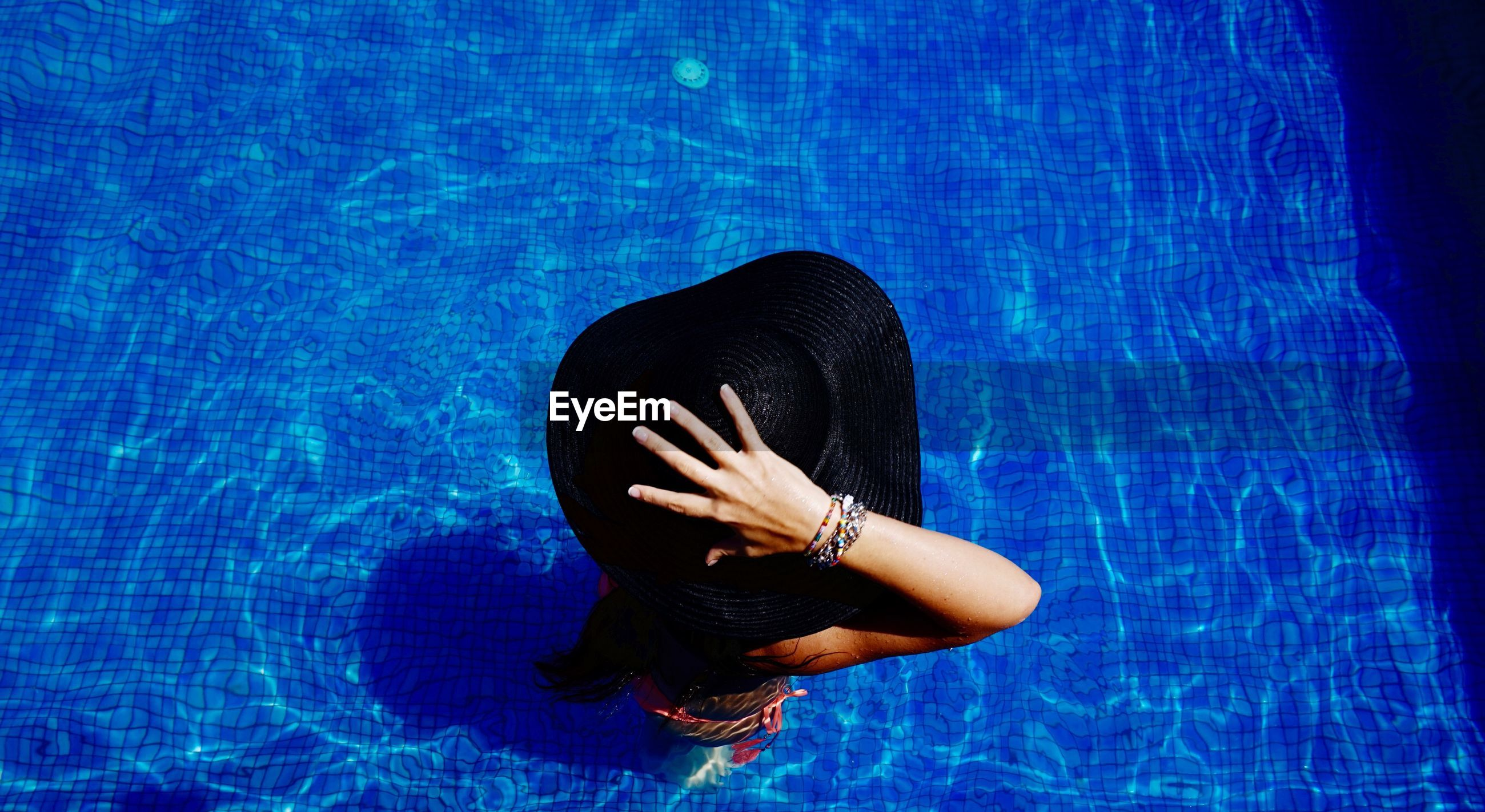 High angle view of woman wearing sun hat in swimming pool