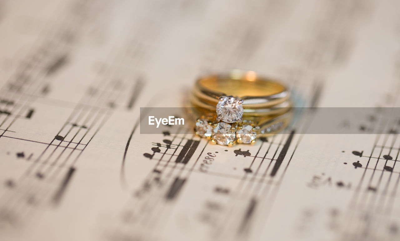 Close-up of diamond rings on musical note