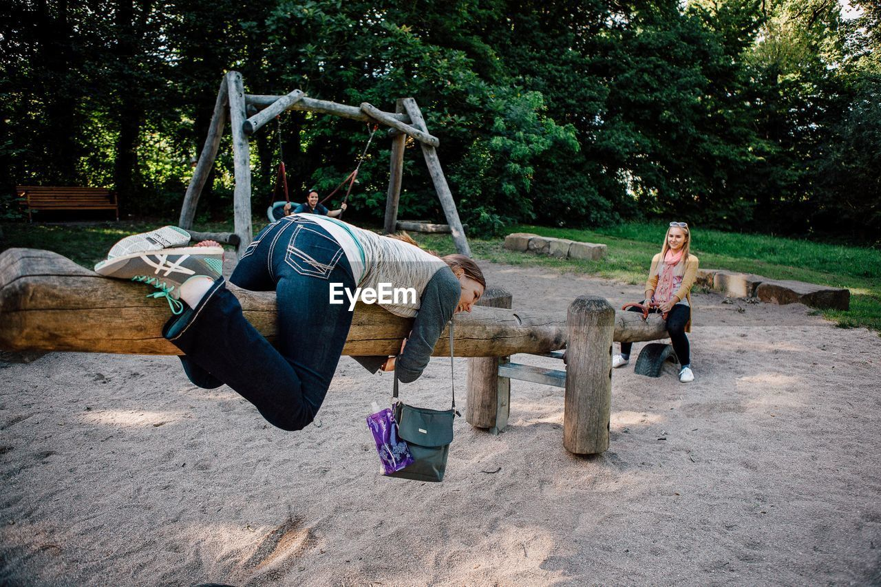 Young female friends playing on wooden seesaw at park