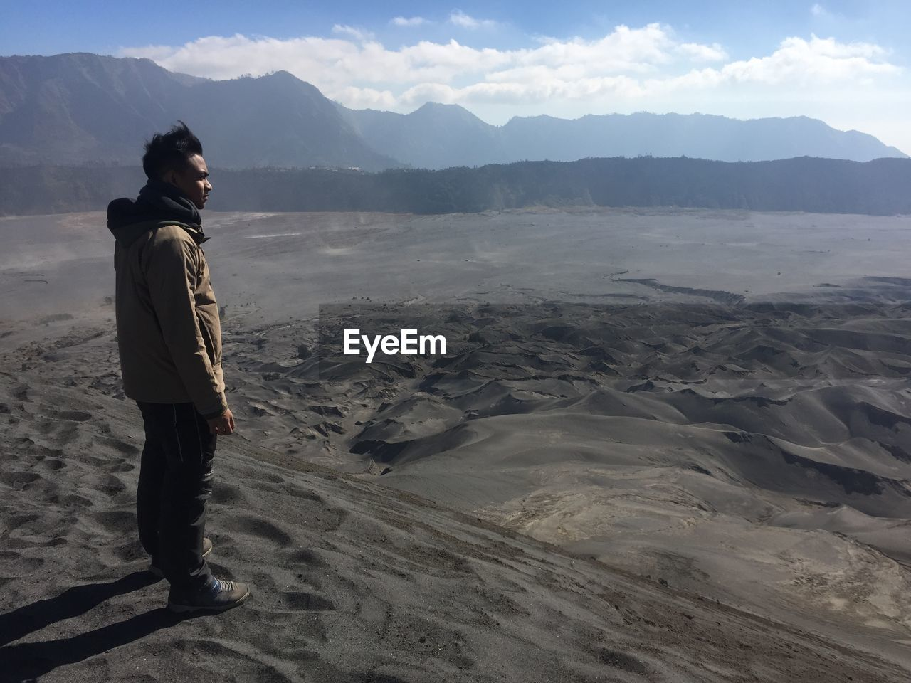 Side View Of Man Standing On Sand Dune In Desert Against Mountains