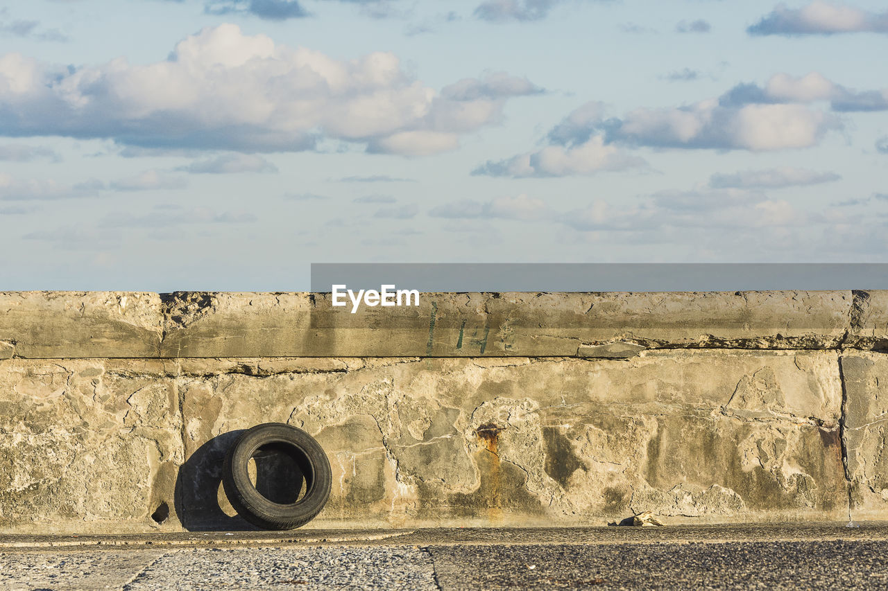 sky, cloud - sky, day, no people, nature, land, wheel, outdoors, metal, old, architecture, wall, field, transportation, wall - building feature, scenics - nature, built structure, tire, sunlight, tranquil scene, concrete