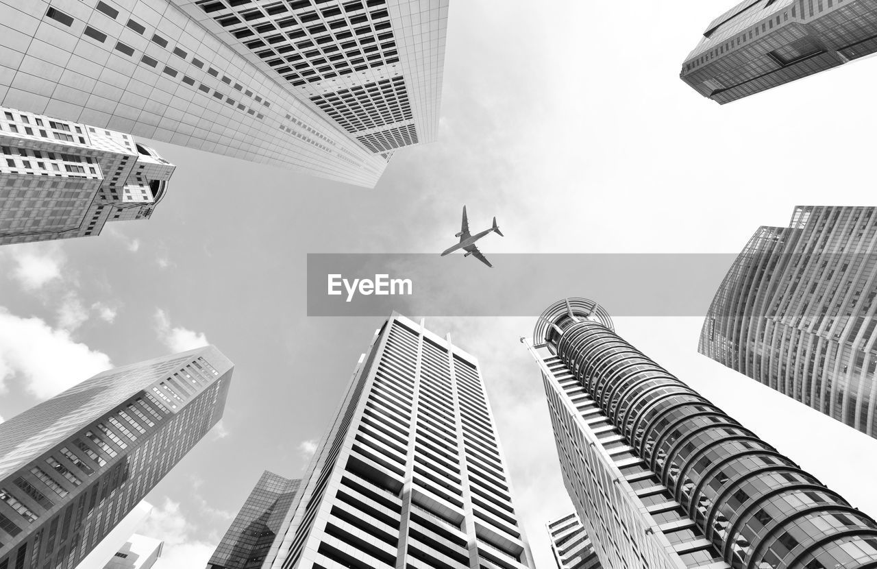 Low Angle View Of Airplane Flying Above Skyscrapers