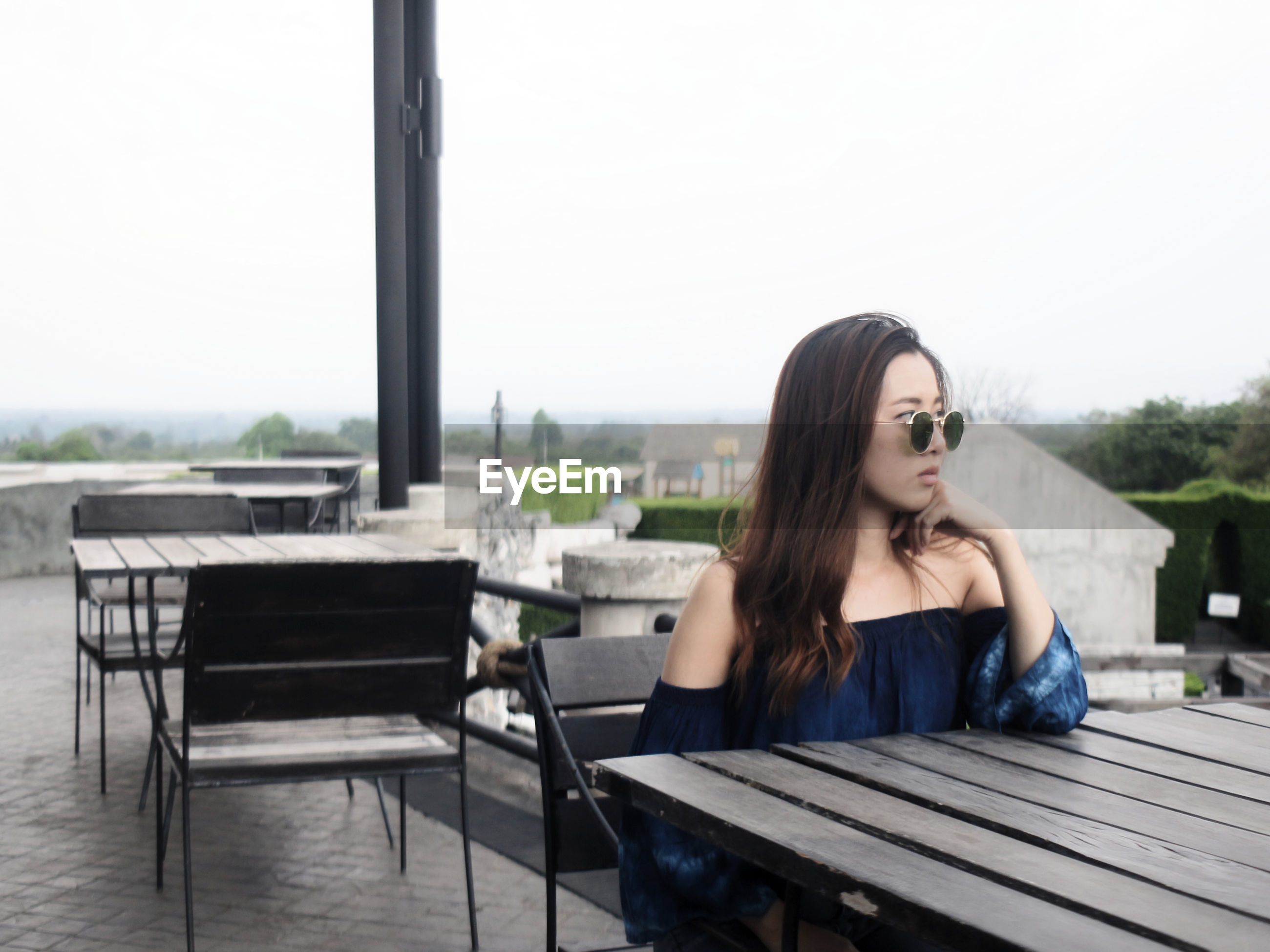Young woman sitting at outdoor cafe against clear sky